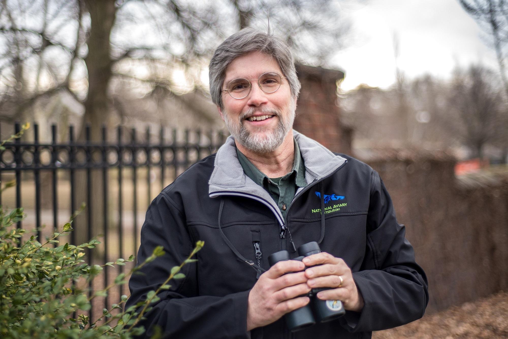 National Aviary Ornithologist Bob Mulvihill smiling holding binoculars