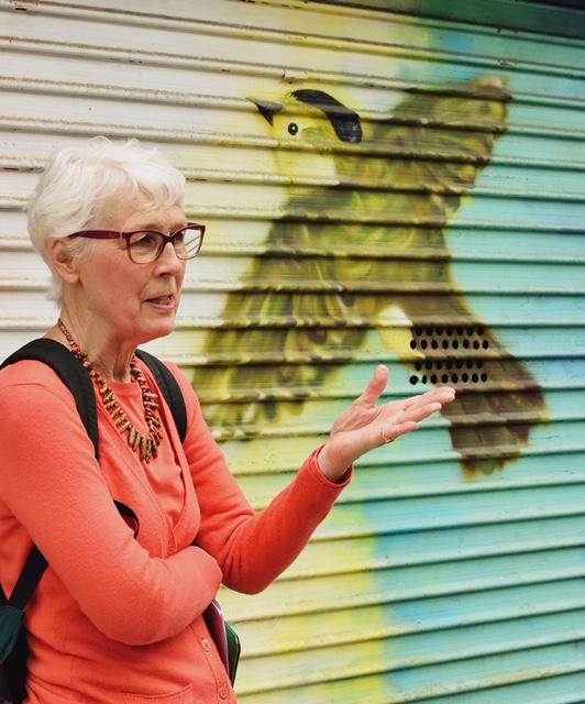 Leigh Hallingby in front of a mural with a bird