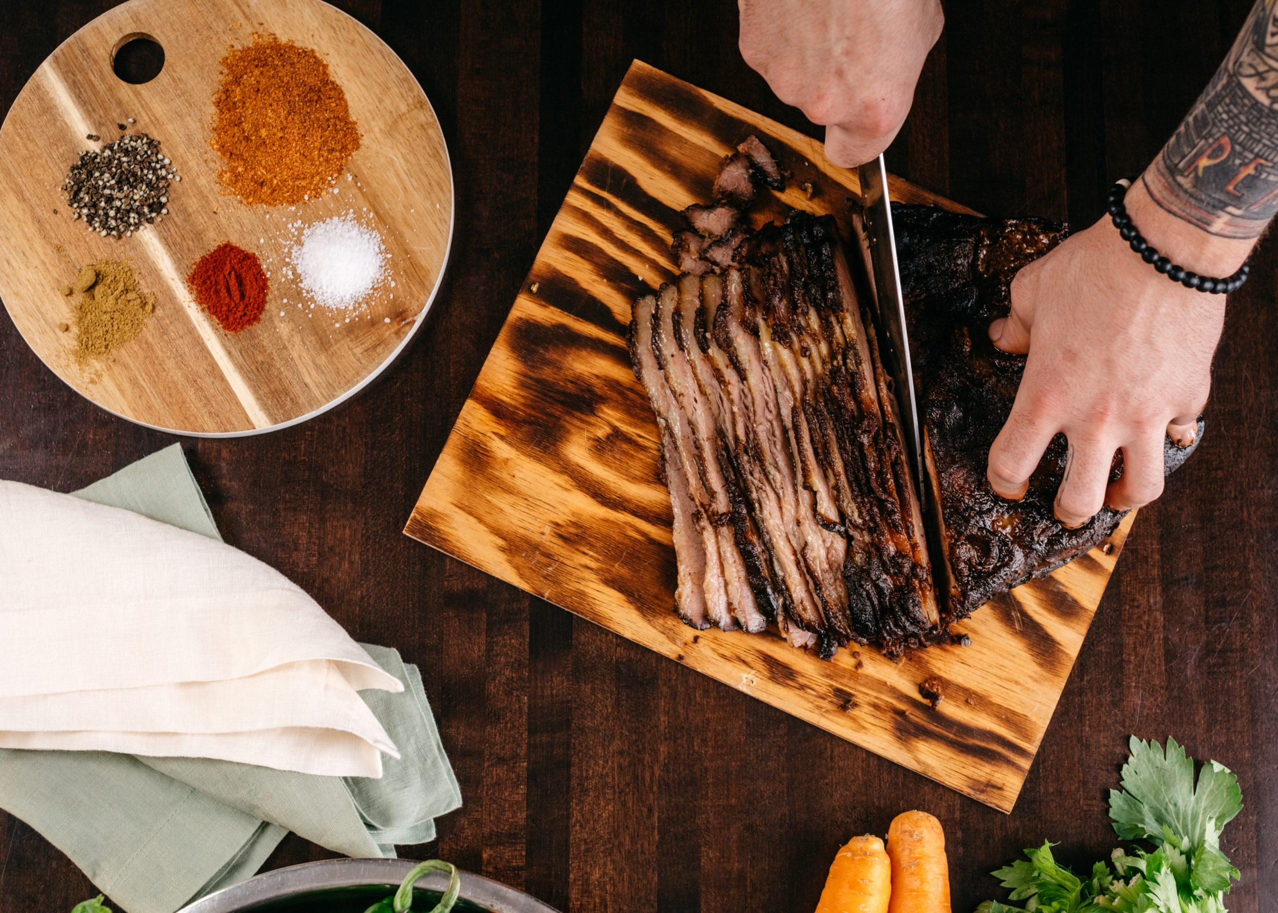 Hands cutting a beef brisket